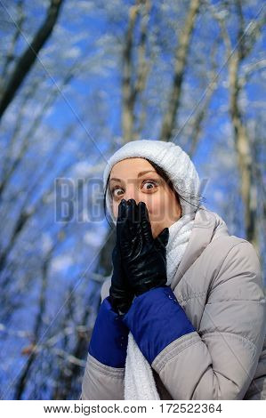 Playful Girl with Large Eyes Hides Smile under Her Hands. Portrait of Surprised Young Woman Enjoying Winter Time Outdoors, HD.