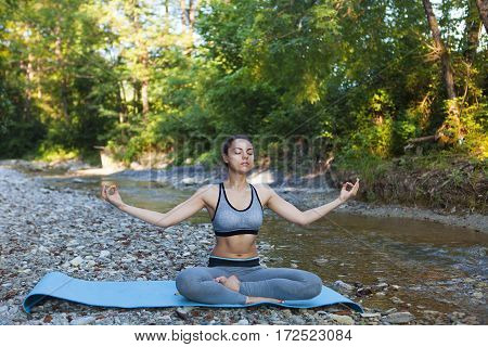 Young Woman Meditating Near The Mountain River. Yoga Practicing Outdoors.