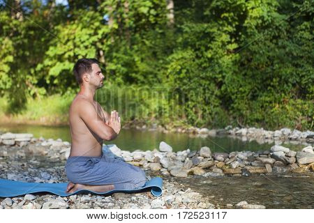 Man Meditating Near The Mountain River. Yoga Practicing Outdoors.