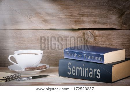 Seminars and Further Training. Stack of books on wooden desk.