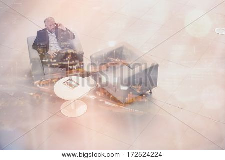Businessman sitting on arm chair and talking on mobile phone in office
