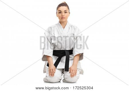 Girl in a kimono sitting on the floor and looking at the camera isolated on white background