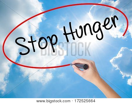 Woman Hand Writing  Stop Hunger With Black Marker On Visual Screen
