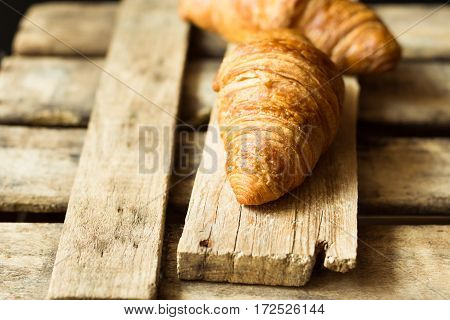 Fresh croissants on aged wood box and plank close up golden crust flaky pastry rustic vintage styleminimalistickinfolk