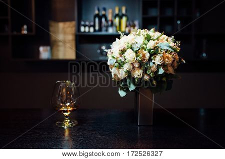 a bridal bouquet of roses near a glass of brandy