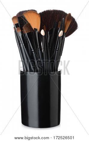 Makeup brushes in black ceramic cup isolated on white