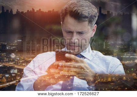 Close up of thoughtful businessman using mobile phone