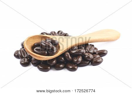 Pile of coffee bean shaped chocolate candies with a wooden spoon over it, composition isolated over the white background