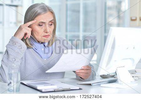senior woman reading document and working with computer