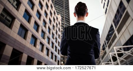 Businesswoman standing against white background against low angle view of office towers