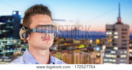 Young man wearing virtual reality simulator against illuminated buildings in city against sky