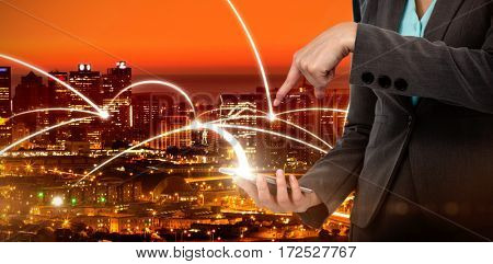 Midsection of businesswoman using mobile phone against high angle view of illuminated cityscape
