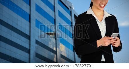 Smiling businesswoman holding mobile phone against reflection on glass building