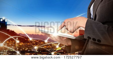 Midsection of businesswoman using digital tablet against illuminated buildings in city against sky