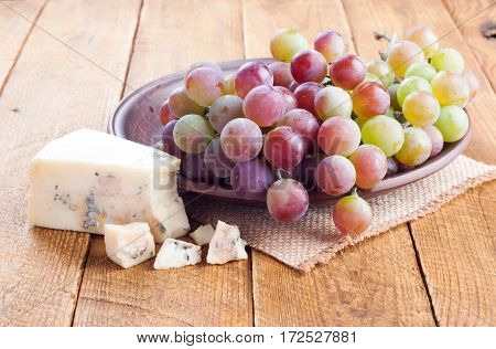 Grapes and blue cheese on wooden background. Tasty snacks. Rustic style