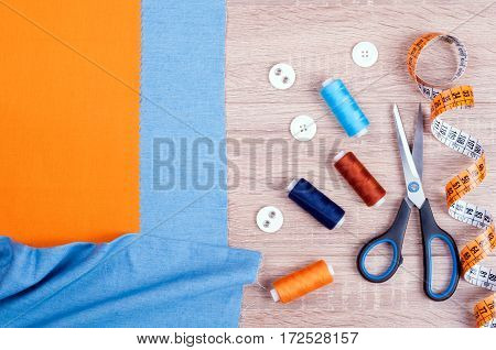 Set for needlework top view. Jeans and cotton fabrics for sewing spool of thread scissors buttons measuring tape and accessories for needlework on old wooden background