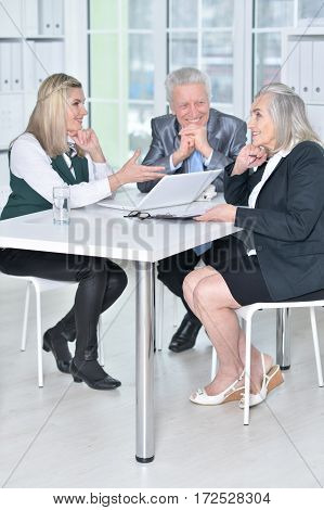 three mature businesspeople using laptop and chatting