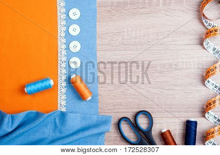 Spool of thread jeans and cotton fabrics for sewing lace measuring tape scissors buttons and accessories for needlework on old wooden background. Set for needlework top view