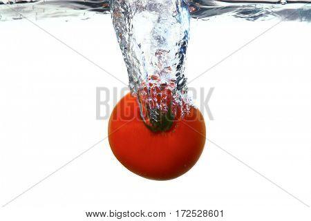 Fesh tomato splashing out of water on white background