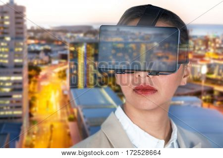 Close up of businesswoman wearing virtual video glasses against illuminated buildings by road in city