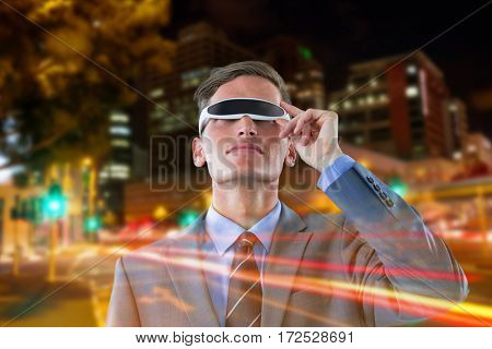 Businessman using virtual reality glasses against white background against illuminated roads by building in city
