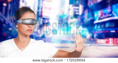 Beautiful woman gesturing while using virtual video glasses against blurry new york street