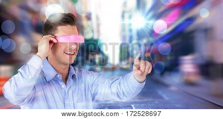 Smiling young man gesturing while using virtual reality headset against blurry new york street