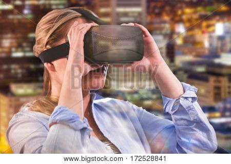 Woman using an oculus against illuminated building in city at night