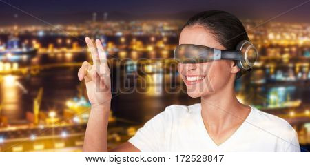 Smiling woman gesturing while using virtual video glasses against illuminated harbor against cityscape