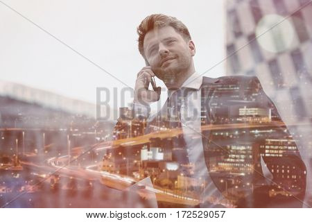 Low angle view of smart businessman talking on mobile phone against office building