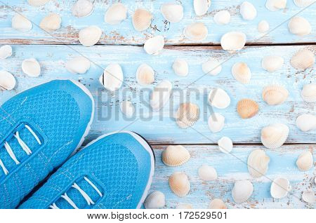 Sport shoes and sea shells on nautical wooden background. Top view sport equipment. Healthy life concept