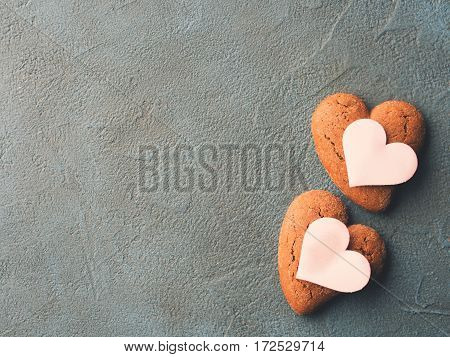 Dark textured concrete background with heart shaped cookies. Your text. top view card