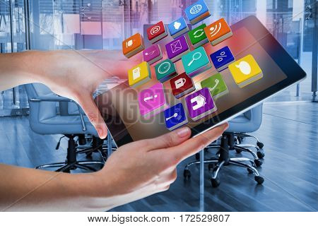 Hands using digital tablet with digital effects against empty chairs in conference room
