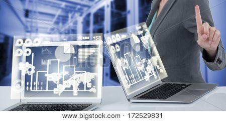 Businesswoman standing by digital laptop against purple vignette