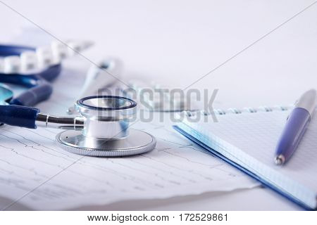Medical stethoscope lying on cardiogram with pile