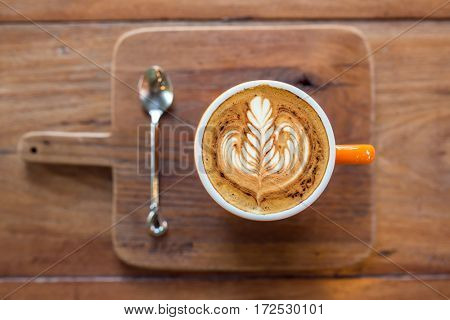 Cappuccino coffee cup served on wooden board top view. Shallow Depth of Field