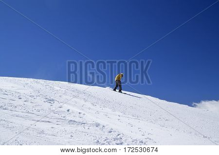 Snowboarder Downhill On Off-piste Slope And Blue Clear Sky