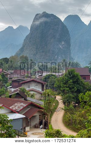 Traditional lao village with mountains on the background near Vang Vieng, Laos