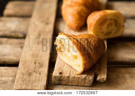 Fresh croissant cut in half with flaky pastry inside visible on aged wood backgroundclose upkinfolk minimalistic