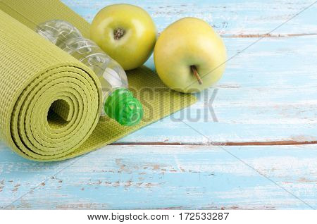 Yoga mat bottle of water and apples on a wooden background. Equipment for yoga. Concept healthy lifestyle diet and sport. Copyspace. Selective focus