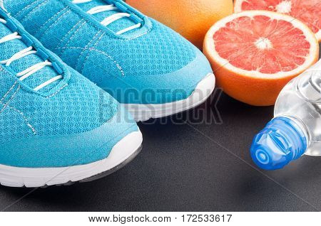 Blue sport shoes sneakers citrus fruits bottle of water on dark background. Sport equipment. Concept healthy lifestyle healthy food sport and diet. Selective focus