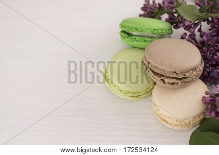 French macarons with twigs of lilacs. Close-up. Background with flowers and macaroons.