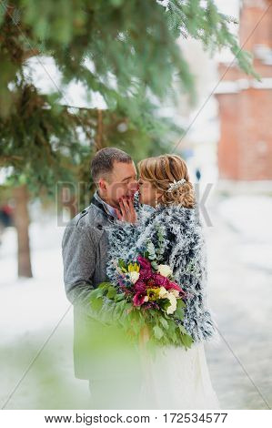 Groom and bride in the cold winter park