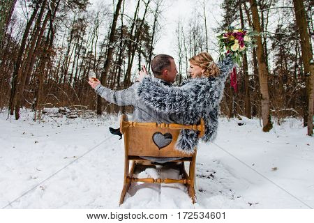 Groom and bride in the cold winter forest with the big wooden sled