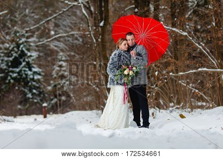 Groom and bride in the cold winter park with a red umbrella