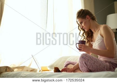 Young beautiful woman sitting in bed with laptop