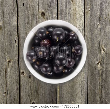 Black currants in a white ceramic bowl. Top view. Ripe and tasty currants on a wooden background. Black currants on wooden table with copy space