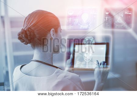Skull and brain graphic on black against female surgeon using digital tablet 3d
