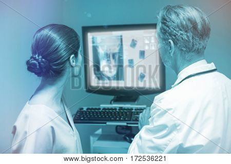 Overhead of a x-ray of a human skull against doctor and nurse examining x-ray on computer 3d