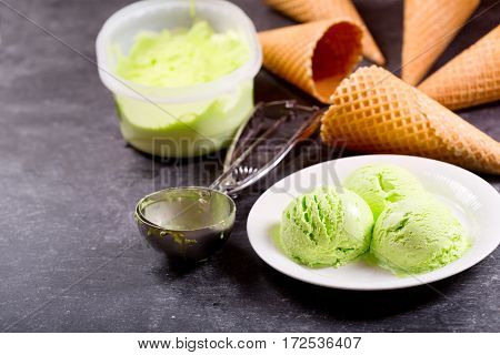 Plate Of Pistachio Ice Cream Scoops And Waffle Cones
